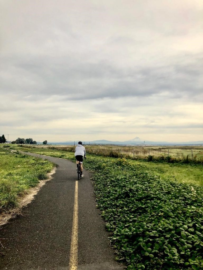 Paul Burke rides his bike on a lonely bike path in the Pacific Northwest, with green grass on either side and mountains in the distance