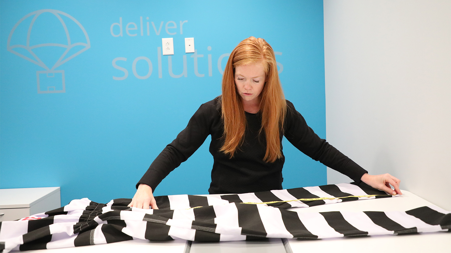 Lonny Carter measures fabric on a desk. The fabric is black and white striped.