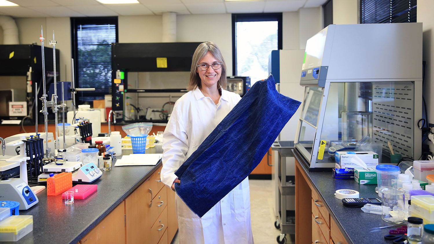 TECS assistant professor Sonja Salmon displays a piece of denim treated with enzymes