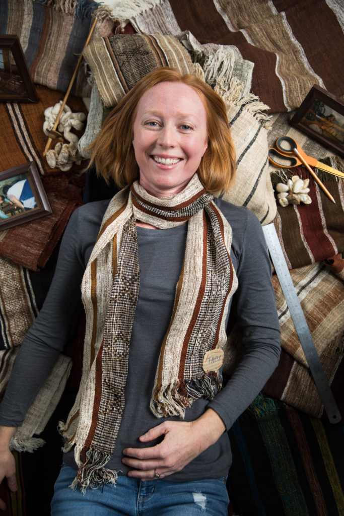 Peace Goods founder Kyley Schmidt, earing and posing on a backdrop of scarves woven from wild Madagascan silk