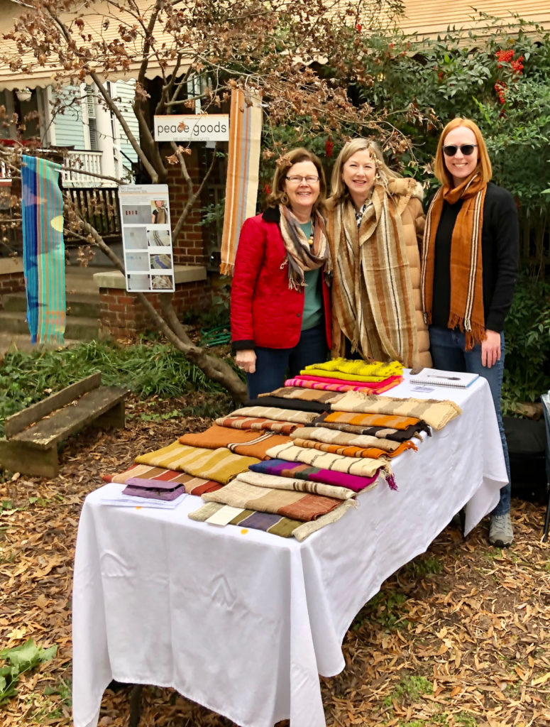 Peace Goods founder Kyley Schmidt and 2 customers at her outdoors table set up at the Boylan Heights Art Walk
