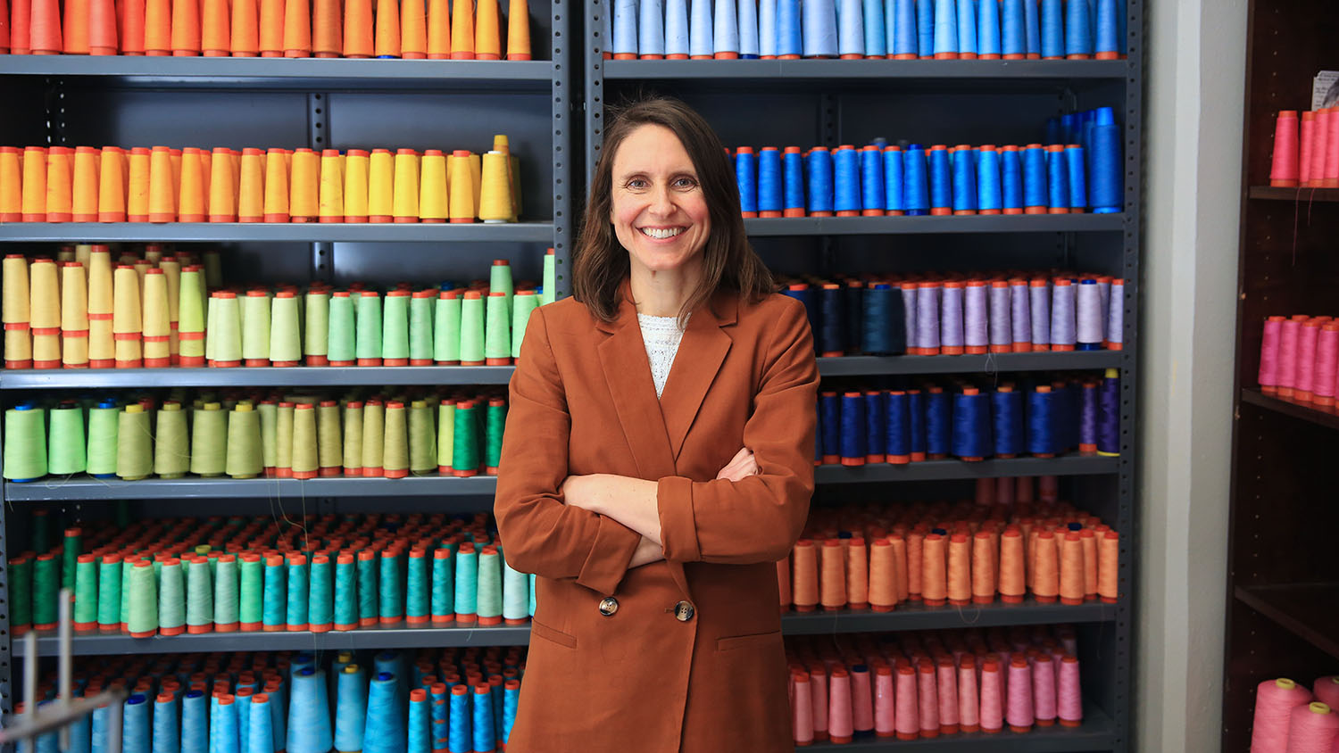 TATM professor Kate Nartker, smiling, stands with arms crossed in front of shelves organized into a rainbow of spools of colored thread