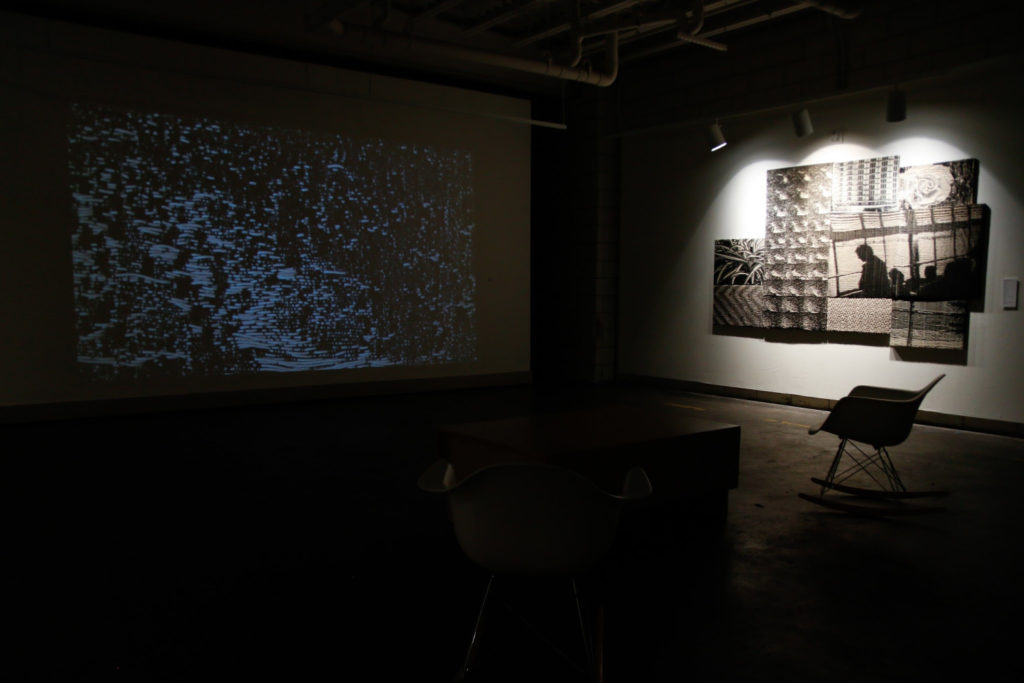 """Photo of a projection and a grouping of Jacquard weavings that look like stills from a black and white movie. Installation by Kate Nartker in the show """"If You Have Ghosts."""""""