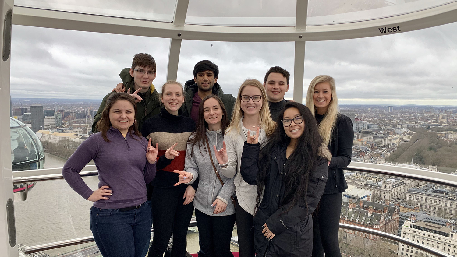 Students pose high above the city of London in a glass observation pod.