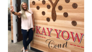 Sarah Wylie posing next to the Kay Yow court