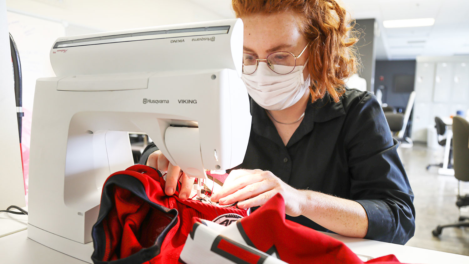 Bailey Knight sews patches onto the Wolfpack football team's uniforms