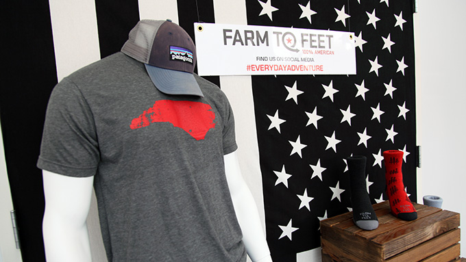 Farm to Feet display showcasing a North Carolina state outline, patagonia hat and black and red socks
