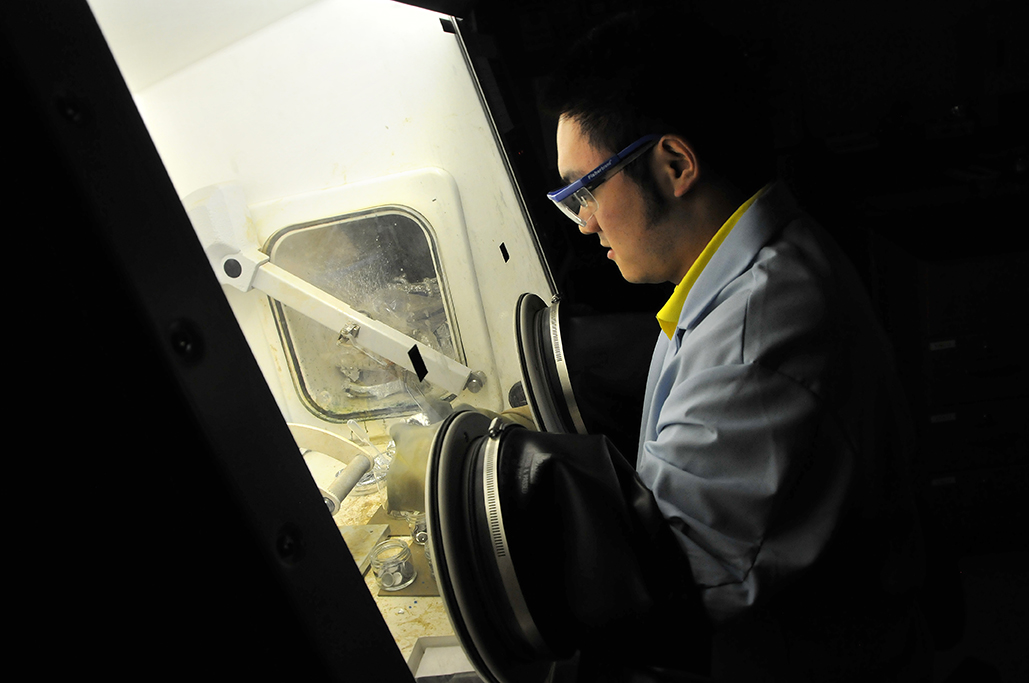 A male student uses a glove box machine located in the Functional Nanofibers Lab