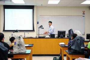 Students observe lecture in lab with microscopes