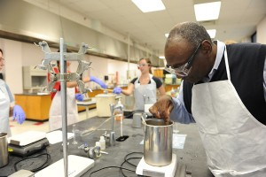 Dr. Freeman observing a solution in a stainless steel beaker