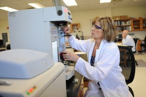 A female in a lab coat and safety glasses sits at a lab machine