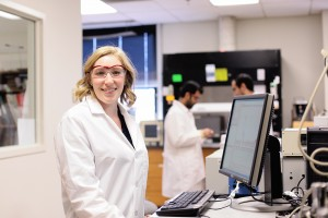 A student stands at a computer smiling in a lab coat and safety glasses