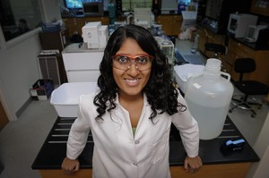 A female student stands smiling in a lab coat and safety glasses