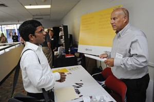 A male student talking to a company representative at a career fair