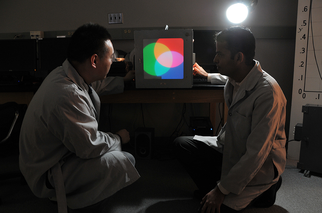 Two male students look at a screen with three overlapping circles that are red, blue, and green