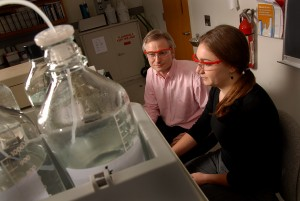 A female student and male professor sit at a lab machine