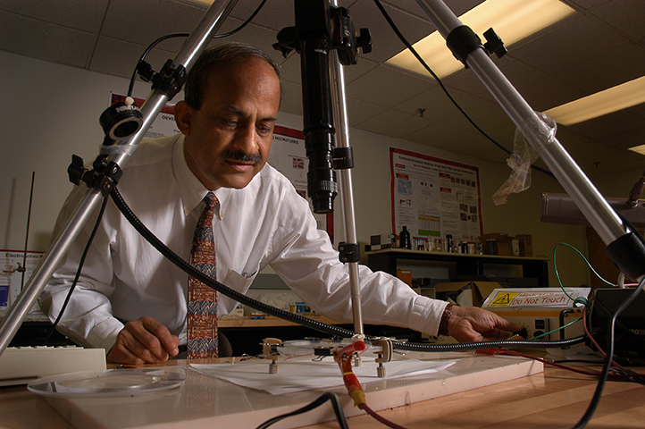 Dr. Ghosh uses an instrument to observe a fiber