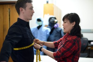 A man is being measure with a tape measure by a female in the TPACC