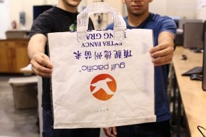Two students hold a bag they designed