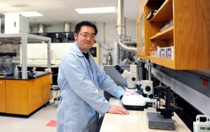 Kun Fu in a lab wearing a lab coat and safety glasses