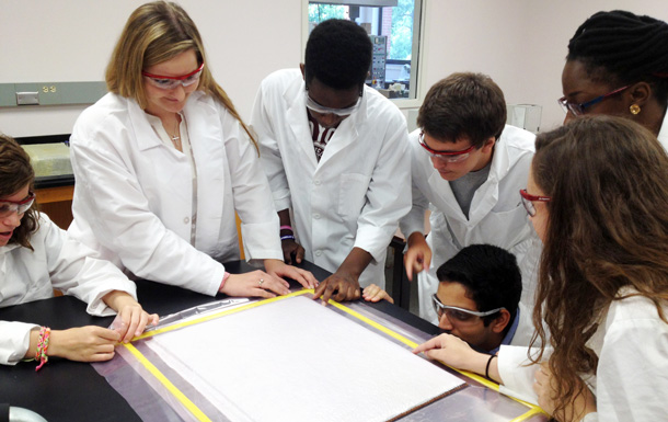STEP students examining the vacuum bag layup of the carbon fiber composite sandwich panel that they assembled.
