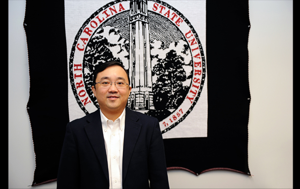 Dr. Zhang stands smiling in front of the NC State University seal
