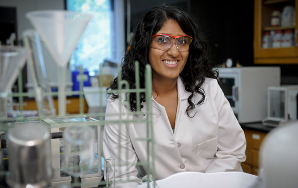 A female student sits smiling in a lab coat and safety glasses