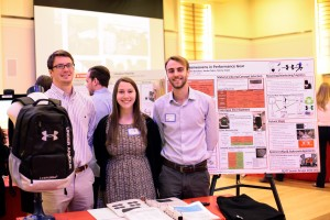 Three senior design students stand smiling in front of their research board