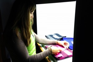 Student observing samples in a light box
