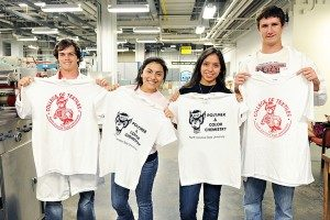 4 Students hold shirts with screen printed designs