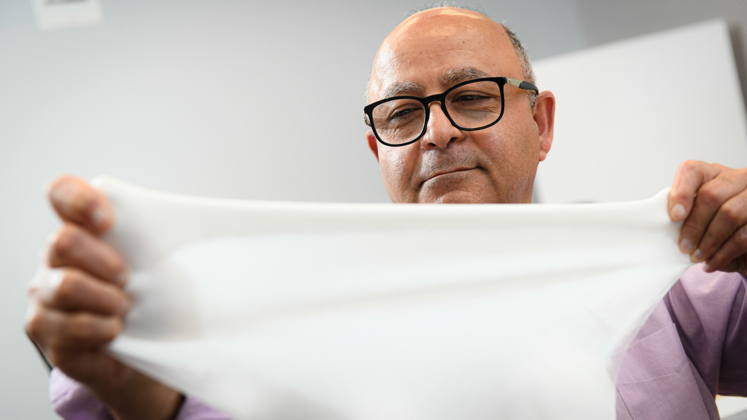 Dr. Behnam Pourdeyhimi holding material