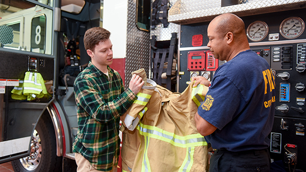 Student works with a firefighter to evaluate protective clothing for comfort and safety