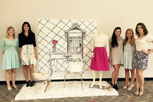 5 female students stand next to a display showcasing a mannequin wearing a pink skirt and white collared shirt