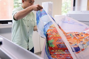 student looking at fabric on digital printer