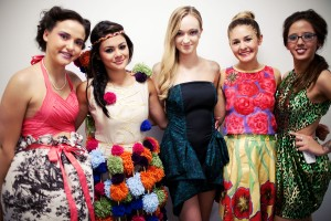 5 female students wearing dresses with different designs including green and black leopard print, flower print, skirts with tree print and a black and blue dress
