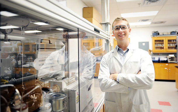Dr. Bradford stands smiling in his lab while wearing a lab coat and safety glasses