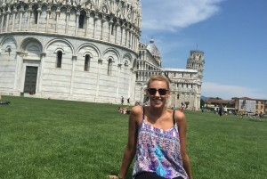Student sitting on grass in front of the Leaning Tower of Piza