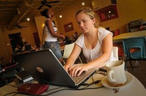 Student working on a laptop in a coffee shop