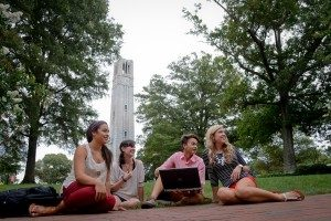 4 Students sitting on grass with NC State Belltower in background