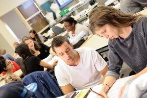 Two students doing classwork together while students in the background sit at tables discussing