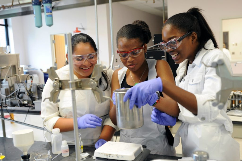 Three female students weighing chemicals in a lab.