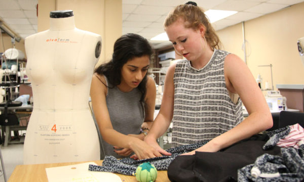 Two students looking at apparel garment