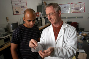 Dr. Martin King shows medical textile to graduate student in lab.