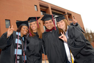 Four graduate students taking a picture together on graduation day.