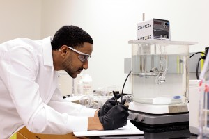 Male student wearing lab coat observes a large glass container on a hot plate