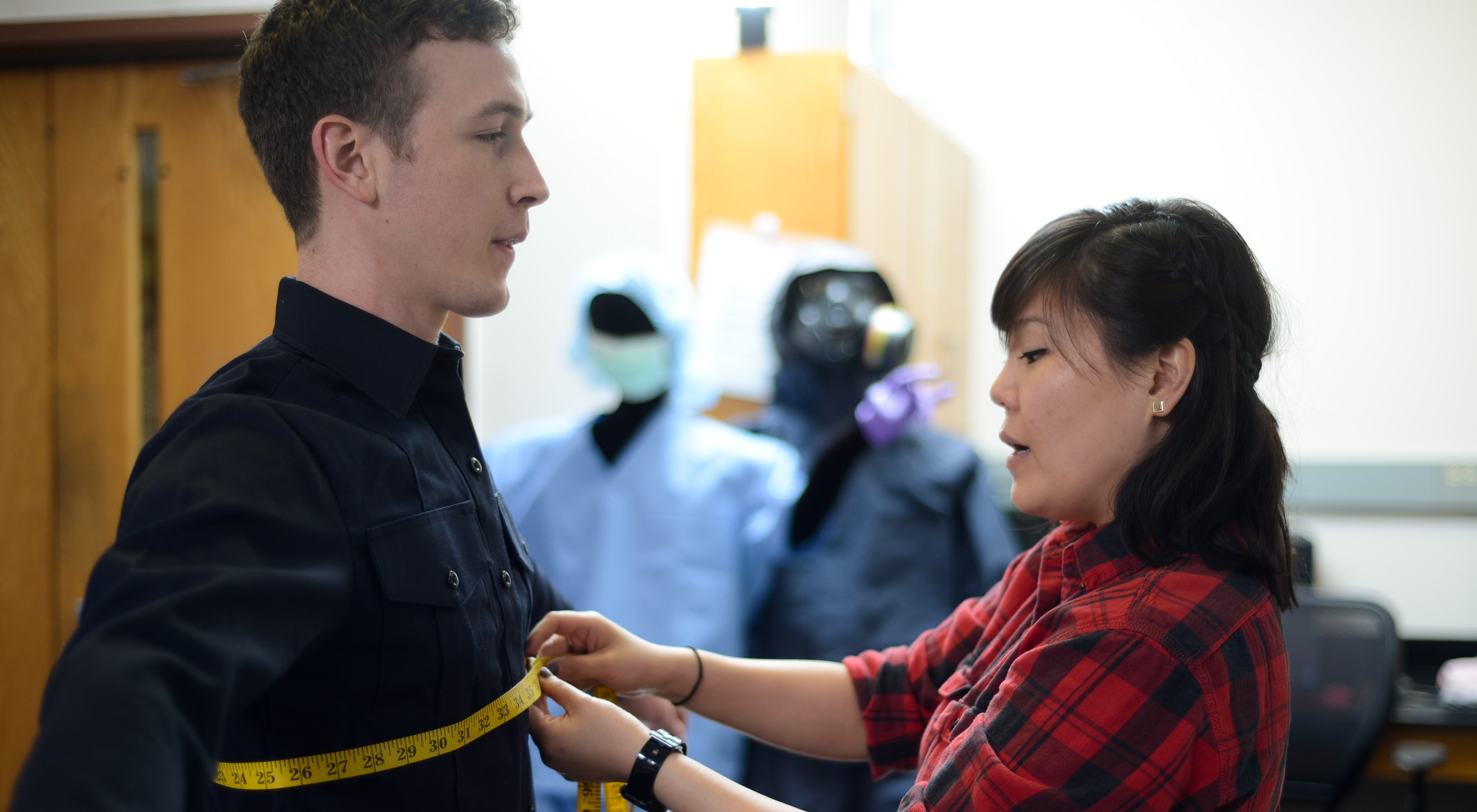 A male being fitted with a tape measure around his chest by a female