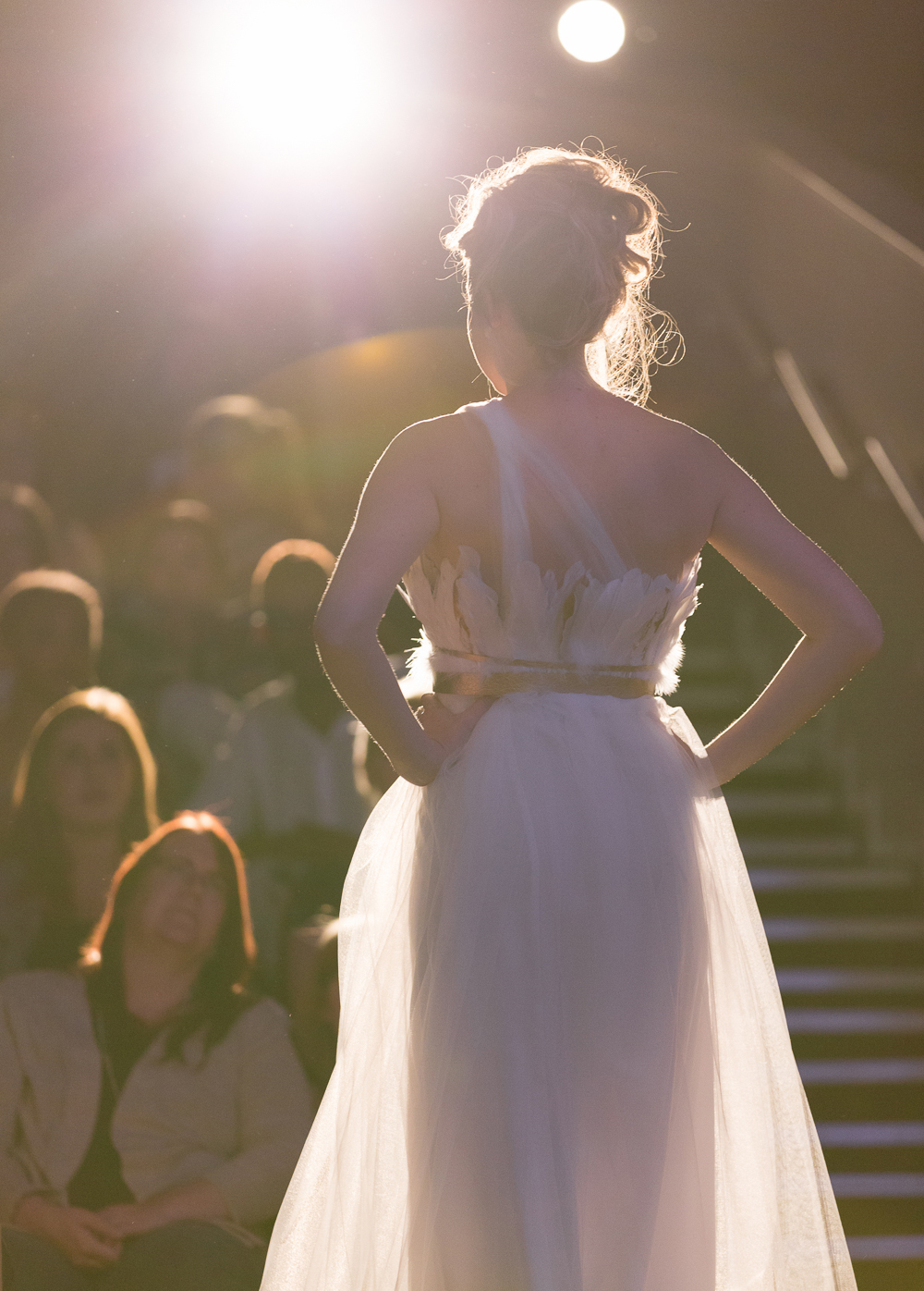 Model at fashion show wears flowing white dress