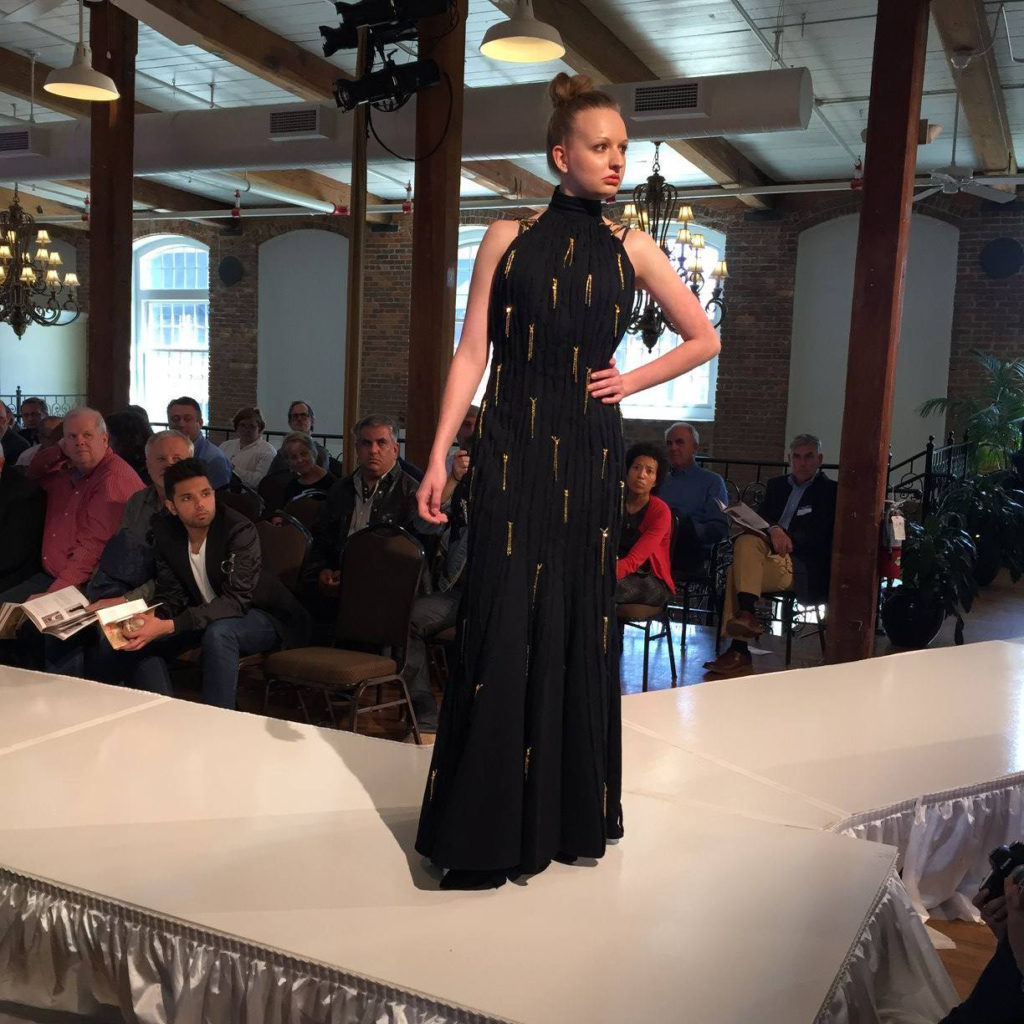 Model on runway wearing a black and gold dress