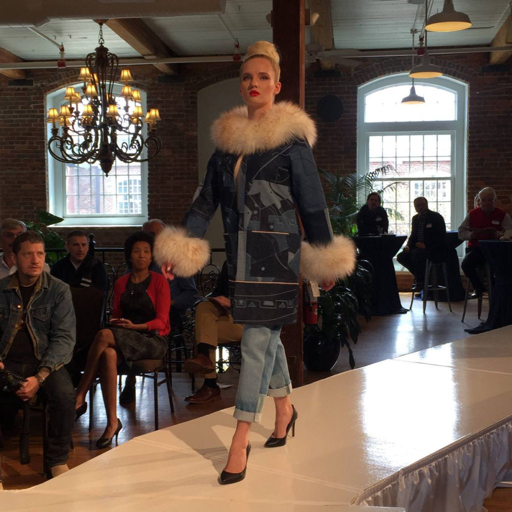 Model on runway wearing a denim coat with fur collar and cuffs