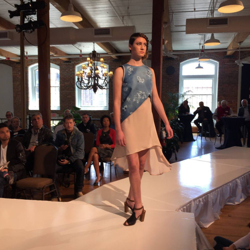 Model on runway wearing a knee length blue and tan dress with white flower designs